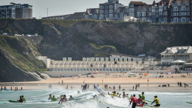 Surfers play in the waves during the hot sunshine on Great Western beach in Newquay, Cornwall in June 2019.