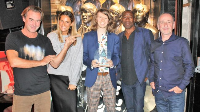 James Hot smiling to camera with his world best song writing award for kindness, surrounded by the judges