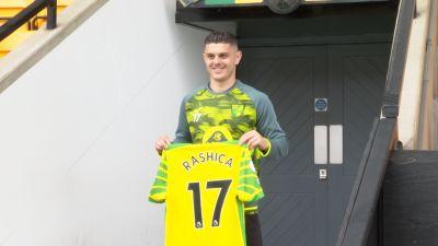 Milot Rashica holds the Norwich City shirt.