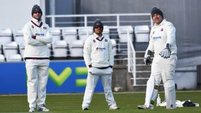 Northamptonshire Cricket Club wearing woolly hats in the field.
