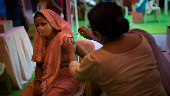 A health worker inoculates a woman during a vaccination drive against COVID-19 in New Delhi, India