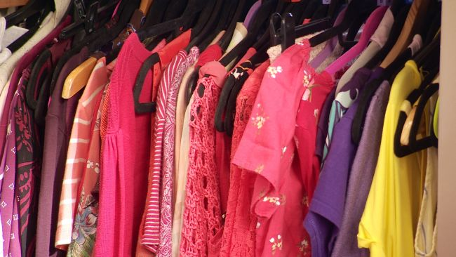 Clothes on a rail in a charity shop.
