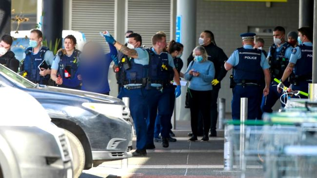 An injured woman being helped by police officers after the stabbing at a supermarket in New Zealand. (Alex Burton/New Zealand Herald via AP)