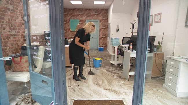 Woman mopping up dirty floor in shop