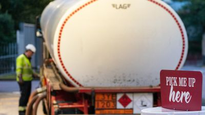 A tanker driver makes a fuel delivery at a petrol station in south London.