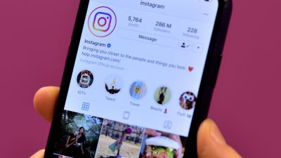 A stock image of a hand folding a phone. On the screen is the Instagram app, showing Instagram's official account.