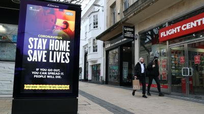 People walk past a 'Stay Home Save Lives' sign on Broadmead in Bristol during England's third national
