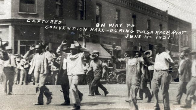 In this photo provided by the Department of Special Collections, McFarlin Library, The University of Tulsa, a group of Black men are marched past the corner of 2nd and Main Streets in Tulsa, Okla., under armed guard during the Tulsa Race Massacre on June 1, 1921.
