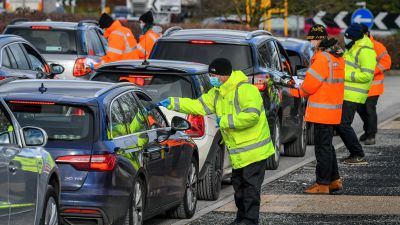 Testing staff hand out kits to motorists attending a surge testing centre at the Science Park, Emersons Green, in Bristol, Gloucestershire.