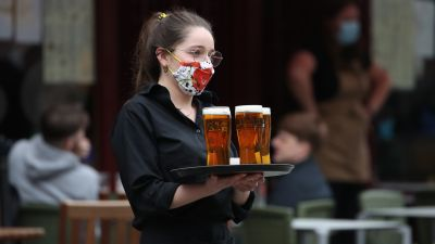 A server carries a tray of drinks from a pub in the Grassmarket in Edinburgh, as beer gardens, non-essential shops, restaurants and cafes, along with swimming pools, libraries and museums in Scotland reopen today after lockdown restrictions have eased. Picture date: Monday April 26, 2021. Andrew Milligan/PA
