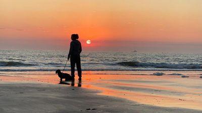 Cromer Sunrise in Norfolk with dog walker