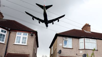 A generic photograph of a plane flying low over a local housing estate, on it's final approach to land on the Northern runway at Heathrow Airport
