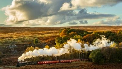 A 1264 locomotive locomotive travels through an autumn scene along North Yorkshire Moors Railway in the North York Moors National Park.
