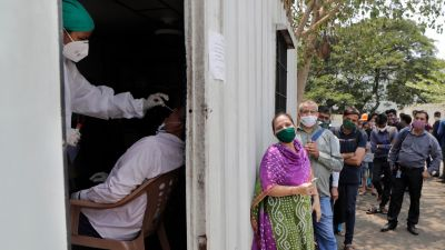 A health worker takes a nasal swab sample of a person to test for COVID-19 as others wait for their turn outside a field hospital in Mumbai, India, Thursday, May 6, 2021. Infections in India hit another grim daily record on Thursday as demand for medical oxygen jumped seven-fold and the government denied reports that it was slow in distributing life-saving supplies from abroad