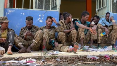 Members of the Ethiopian National Defense Force who were captured by Tigray forces sit on the ground inside a prison