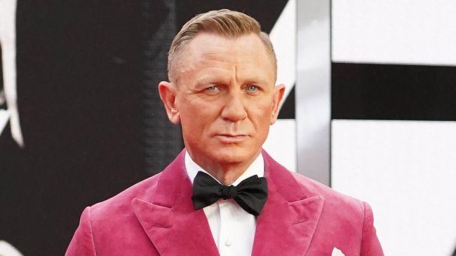 Daniel Craig in pink jacket on red carpet at Bond premier
