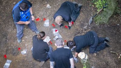 The specialist officers marking up an area of groundand taking items for further examination.