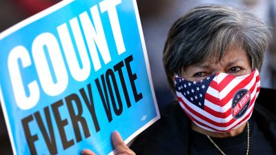 Volunteer election poll worker Cecilia Chaboudy-Dow joins demonstrators as they stand across the street from the federal courthouse in Houston, Monday, Nov. 2, 2020, before a hearing in federal court involving drive-thru ballots cast in Harris County.