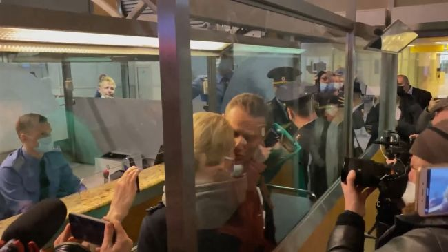 Alexei Navalny kisses his wife goodbye as he is arrested after arriving in Moscow.