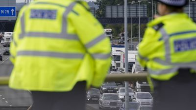 Police officers watch the M25 motorway near Heathrow Airport for Insulate Britain protestors who…