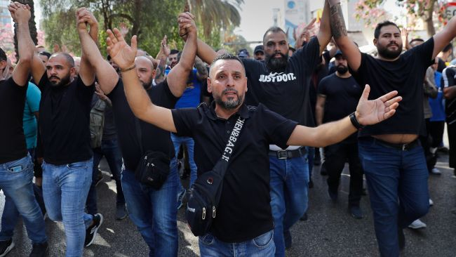 Supporters of the Shiite Hezbollah and Amal groups chant slogans against Judge Tarek Bitar.
