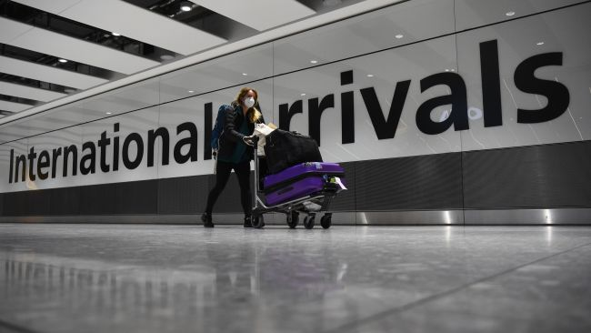 EMBARGOED TO 0001 SATURDAY AUGUST 21 File photo dated 18/01/21 of a passenger pushing luggage through the Arrival Hall of Terminal 5 at London's Heathrow Airport. Holidaymakers have been subjected to 50 changes in the rules for international travel since the first coronavirus lockdown, according to new analysis by PA Media. A similar number of changes have occurred in Scotland, Wales and Northern Ireland as the devolved administrations have largely mirrored England's rules. Issue date: Saturday August 21, 2021.