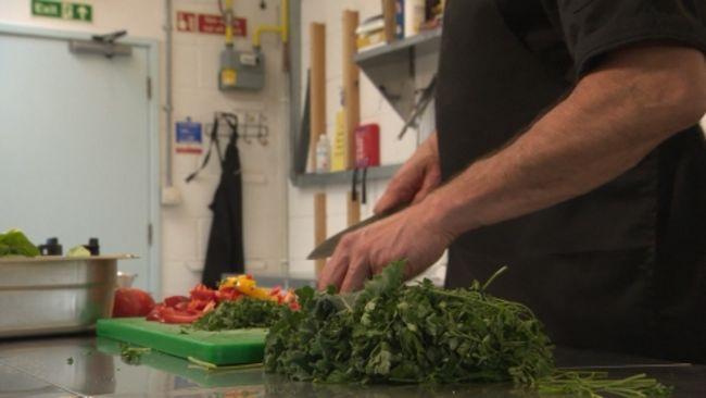 man chopping fresh kale