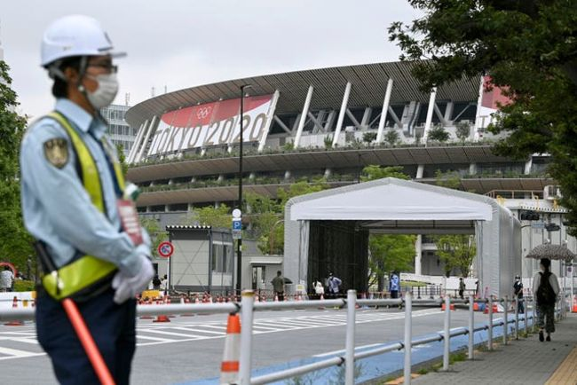 A security worker stands near the Olympic stadium in Tokyo