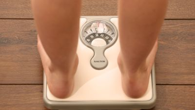 A person stands on weighing scales