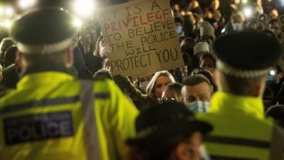 A woman holds up a placard as people gather in Clapham Common, London, after the Reclaim These Streets vigil for Sarah Everard was officially cancelled.