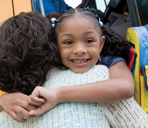 Girl-at-schoolbus-hugs-woman