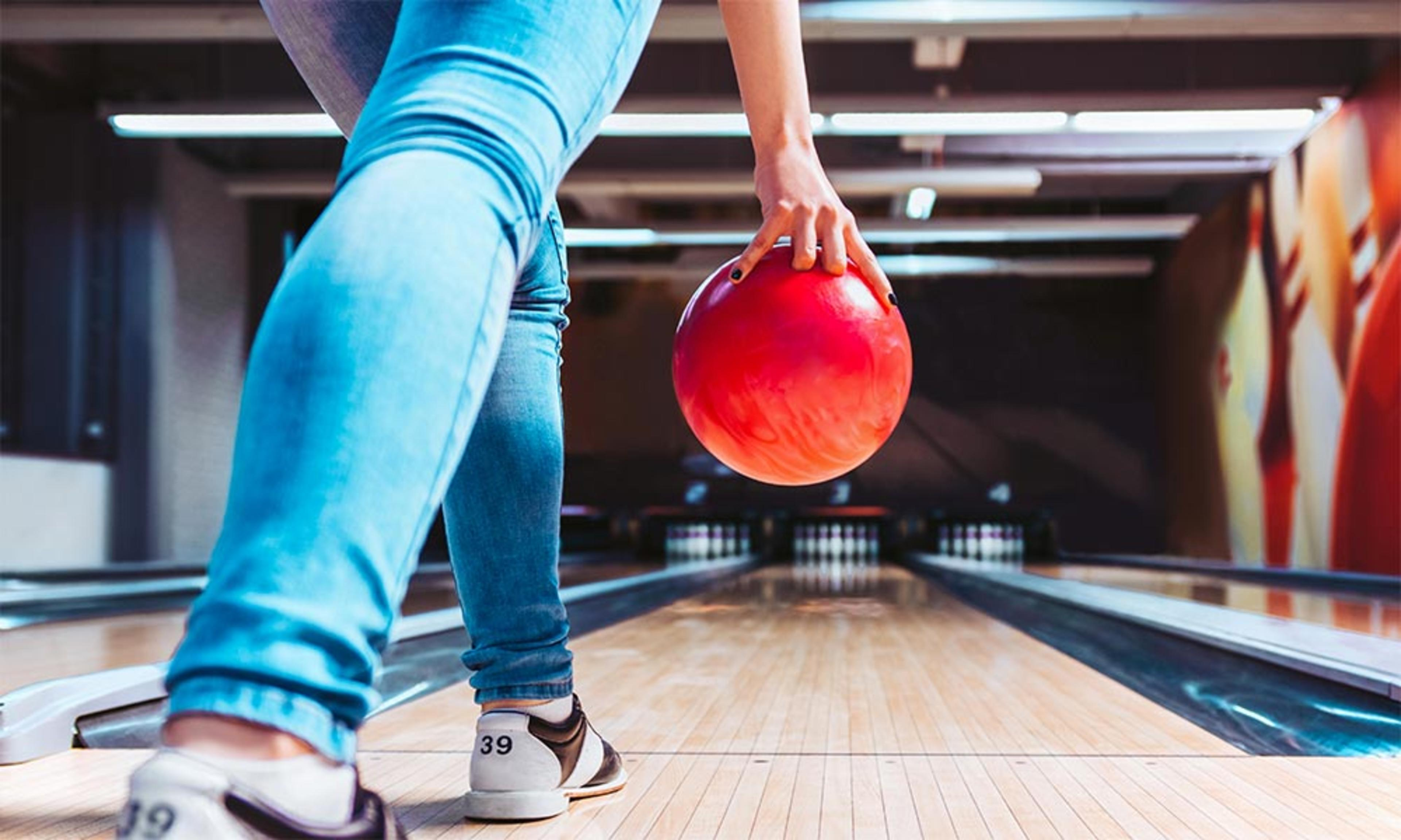 A woman in blue jeans ten-pin bowling with a red bowling ball