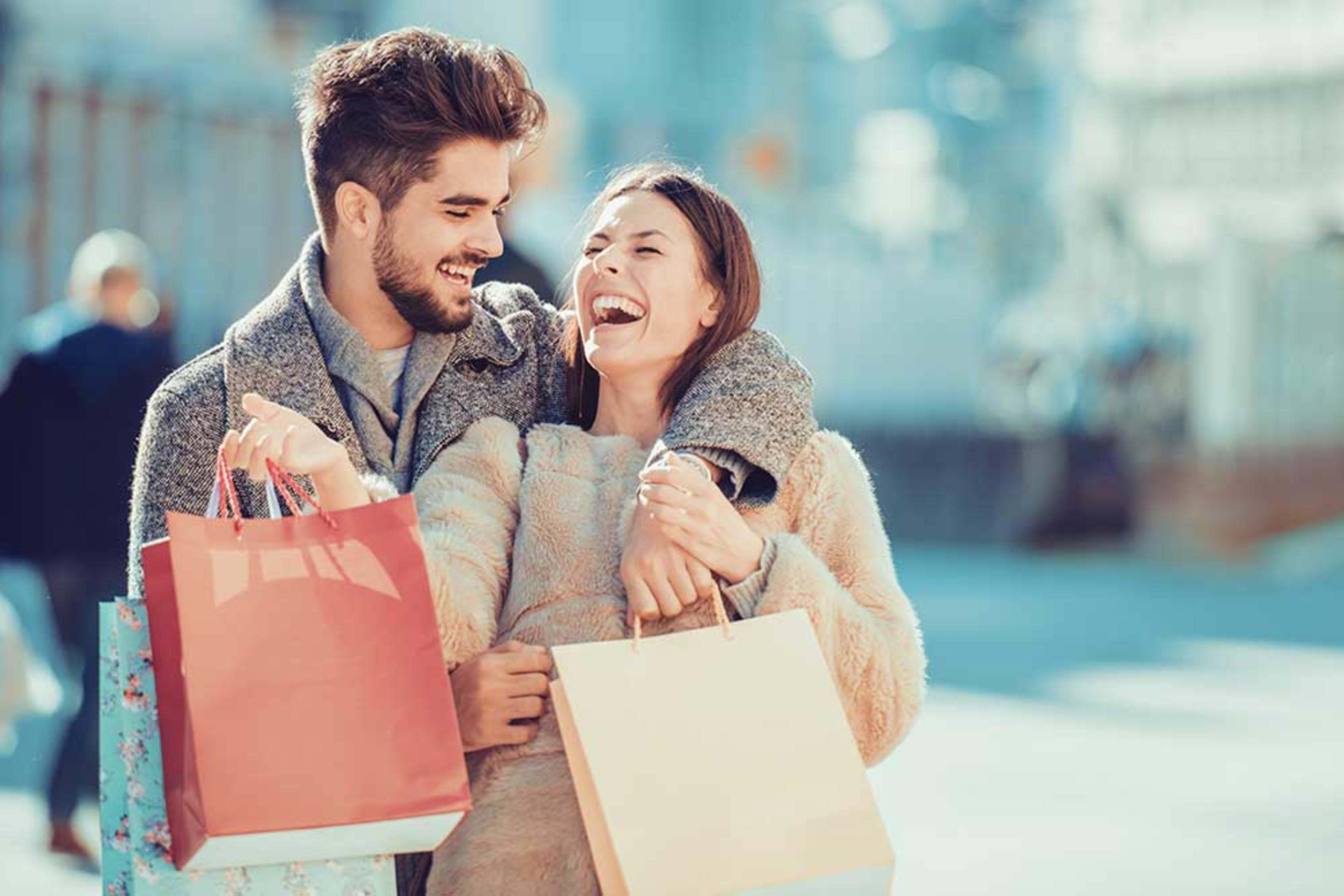 Man and woman laughing together while holding shopping bags