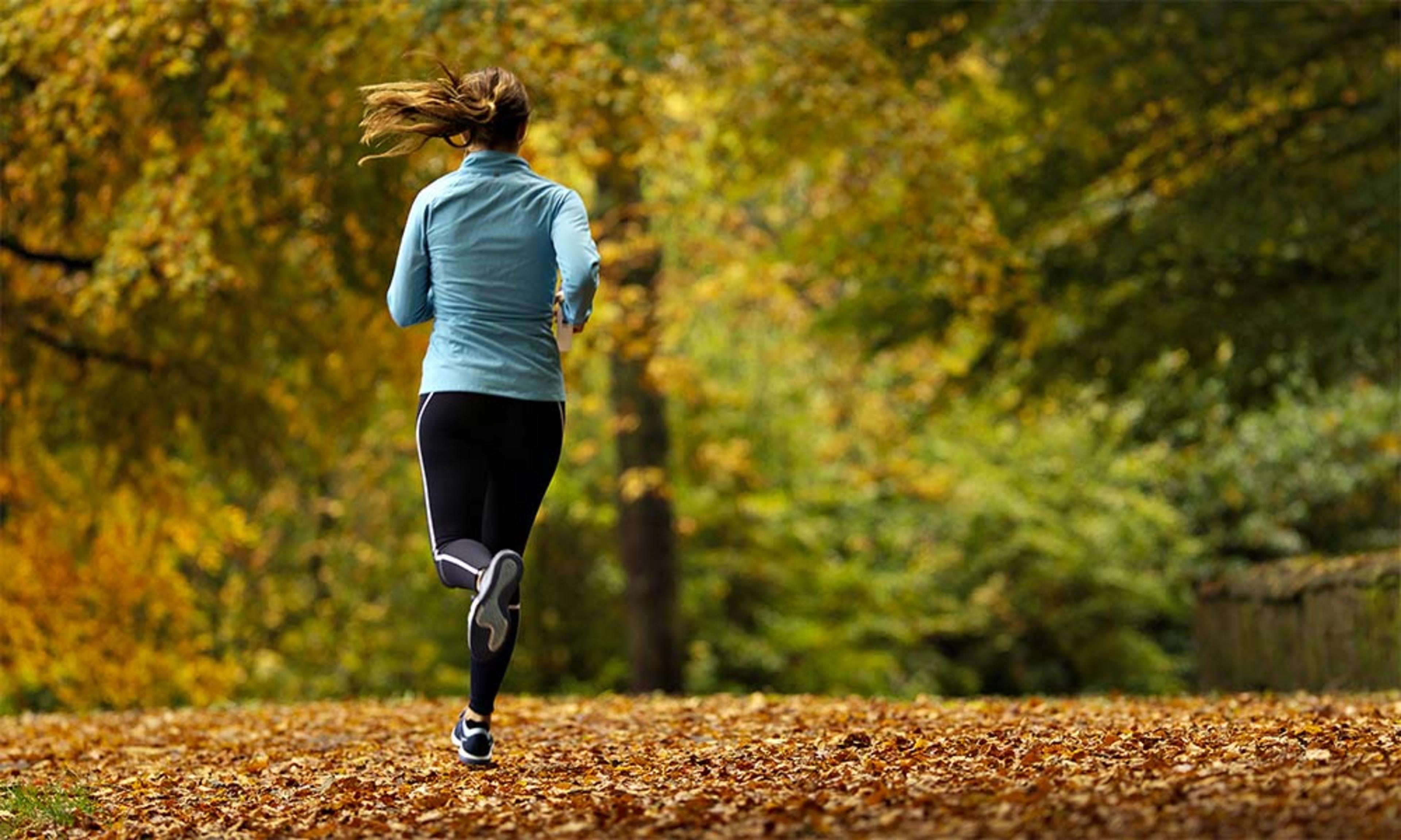 Woman jogging through a leafy park