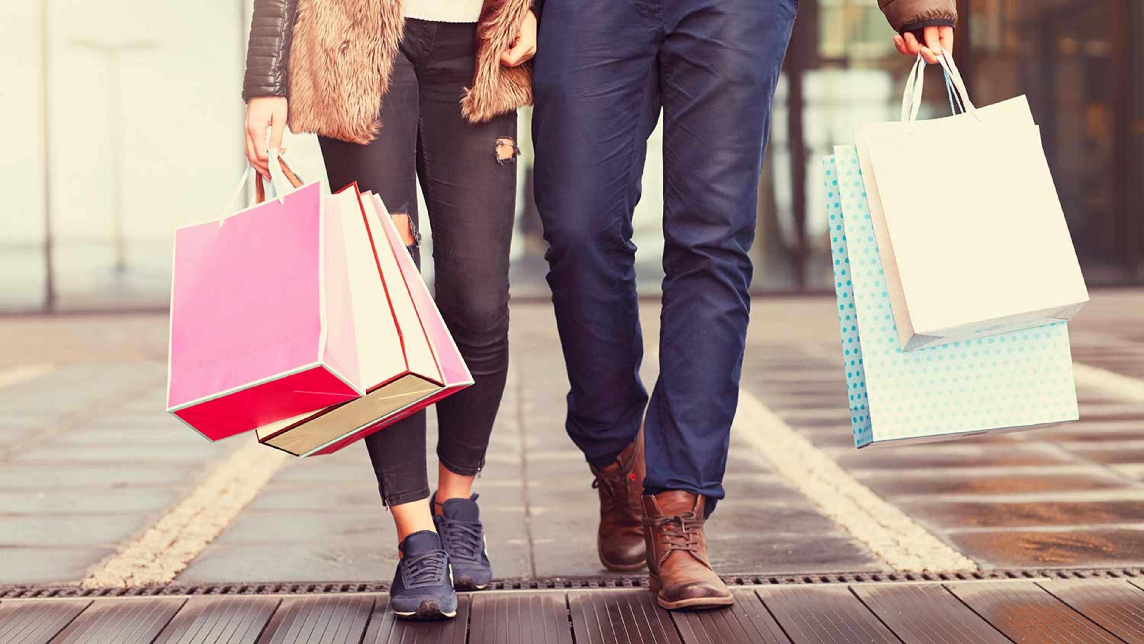 Couple walking along street holding shopping bags