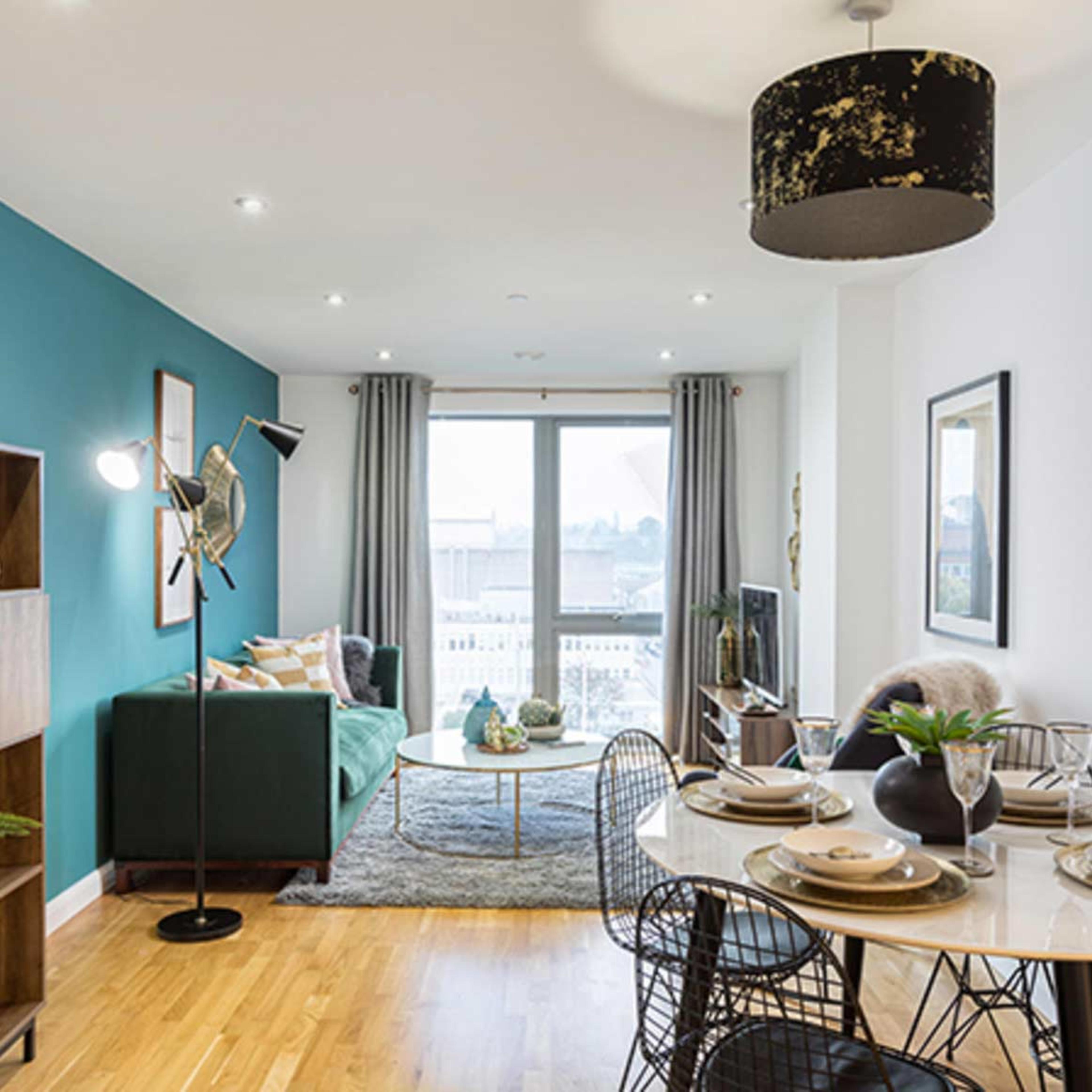 An open plan new build apartment living and dining area with dining table, sofa and full height window