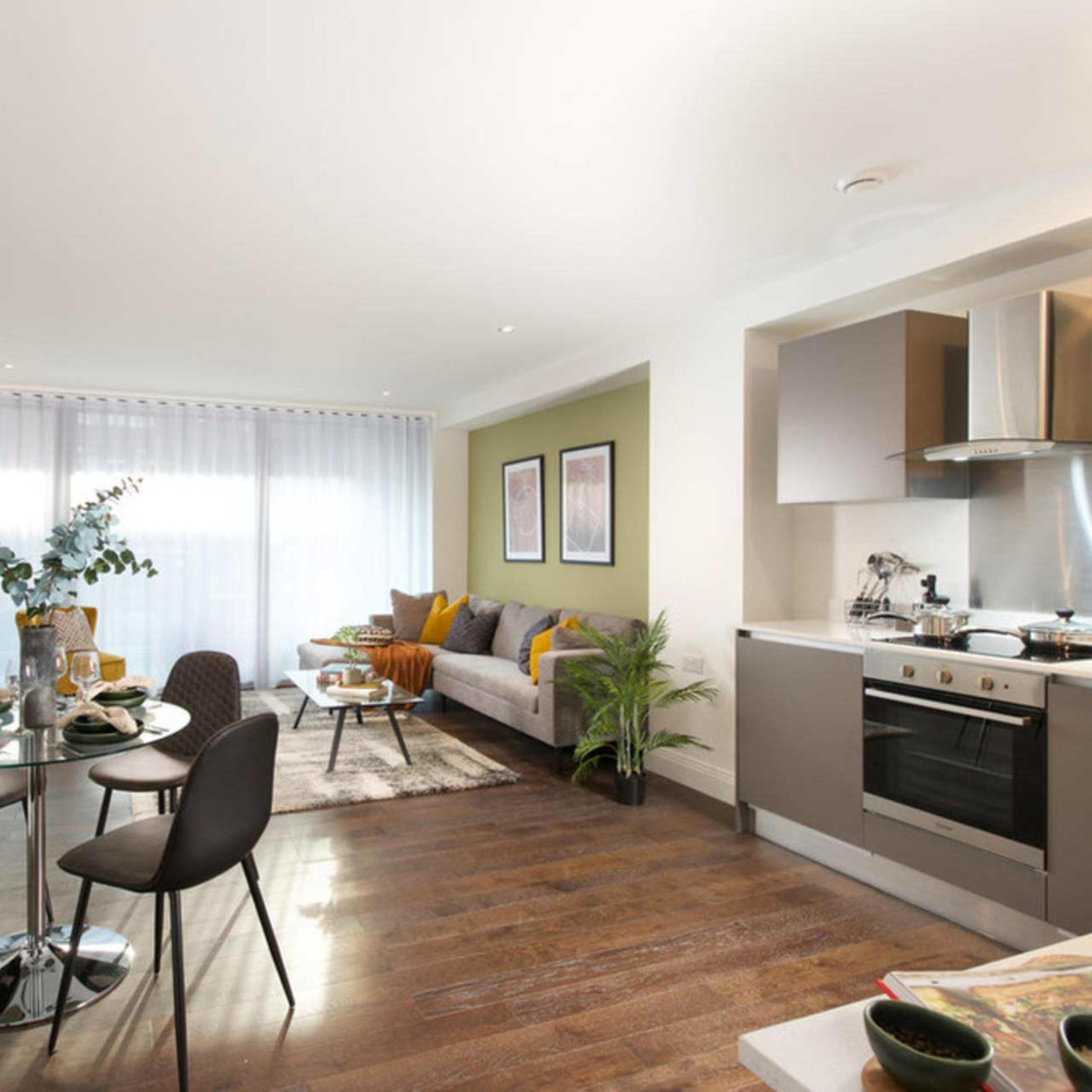 An open plan living area in an apartment with wood effect flooring and full height windows