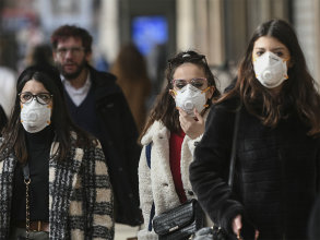 Women in Milan, Italy, wear masks while walking outdoors in February 2020, in an attempt to protect themselves from the coronavirus that causes COVID-19.