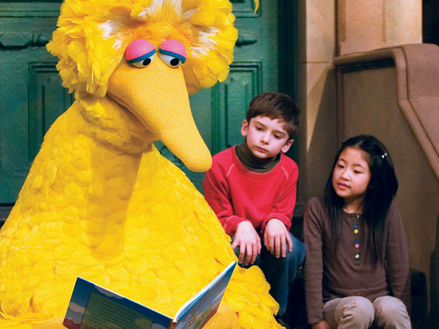 Big Bird reading a storybook during a taping of Sesame Street, 2008. Mark Lennihan, AP Images.