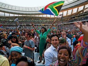 A woman waves a South African flag during a memorial service that celebrated the life of Nelson Mandela, the country's beloved former president, in Cape Town Stadium on December 11, 2013.