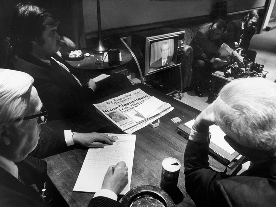 Reporters watching Richard Nixon on TV during Watergate.