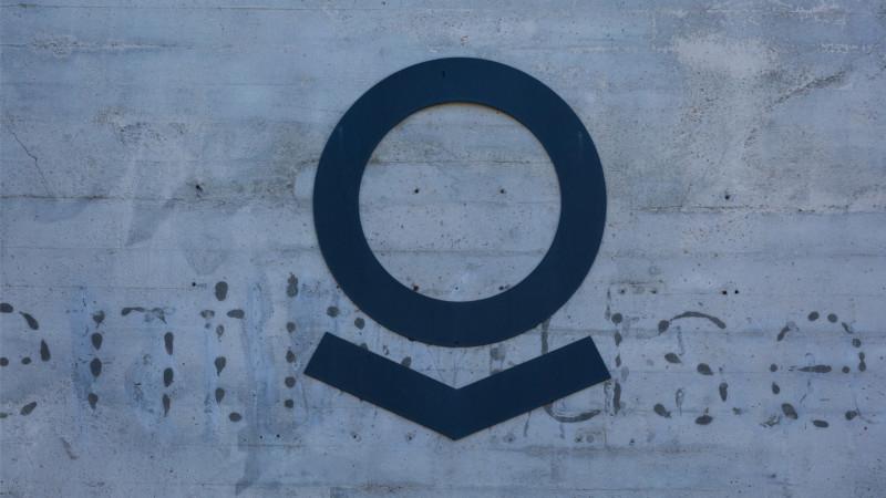 Palantir logo on the grunge concrete wall of Palantir Technologies cafeteria