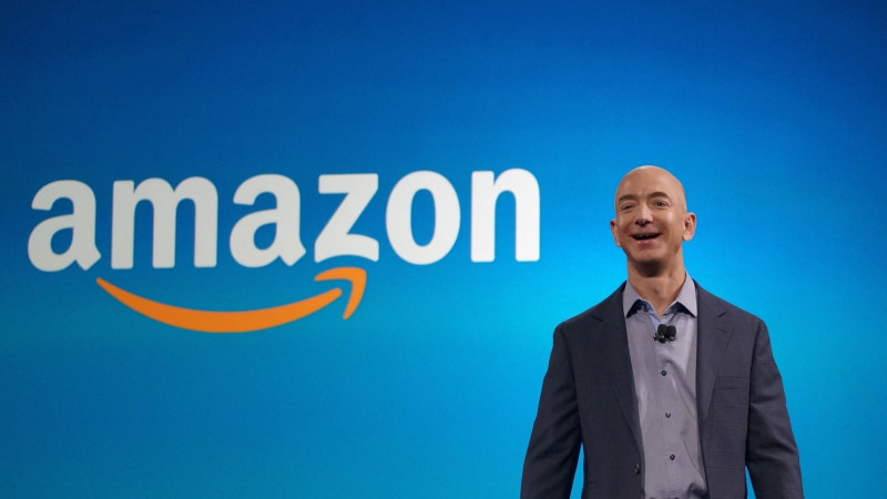 Amazon CEO Jeff Bezos laughs in front of the company's logo.