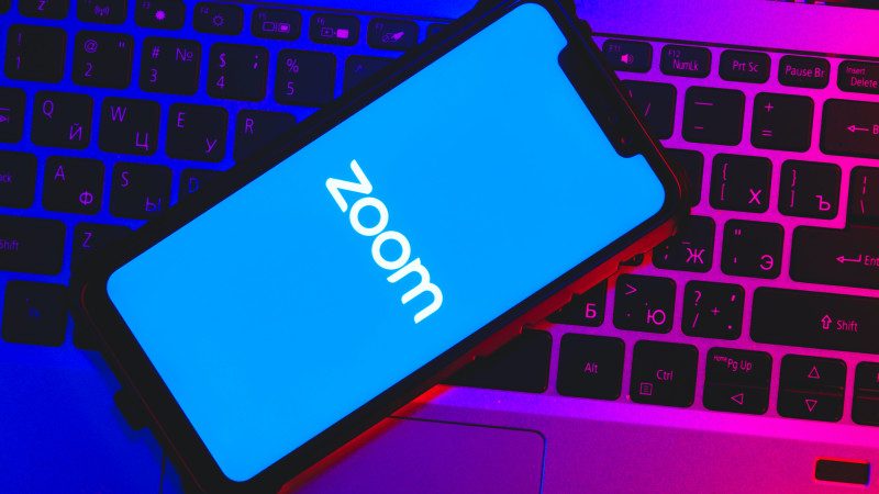 Zoom logo on a phone that is lying on a laptop