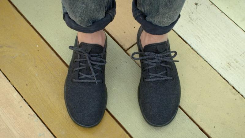 allbirds black shoes on wooden deck