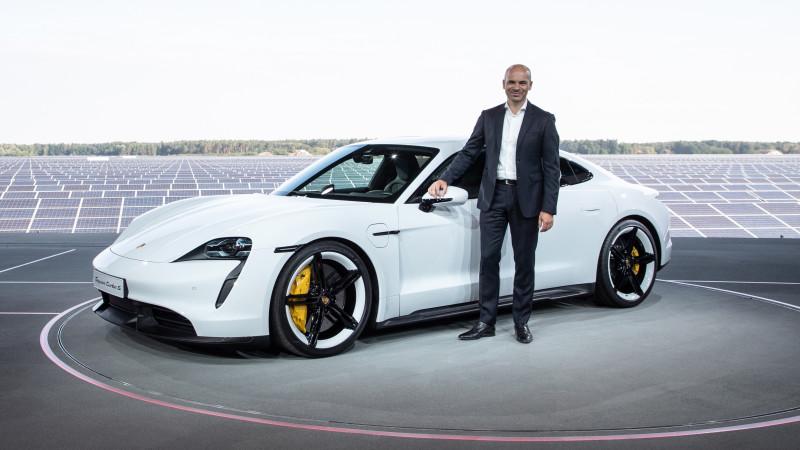 Manfred Harrer standing next to a Porsche Taycan