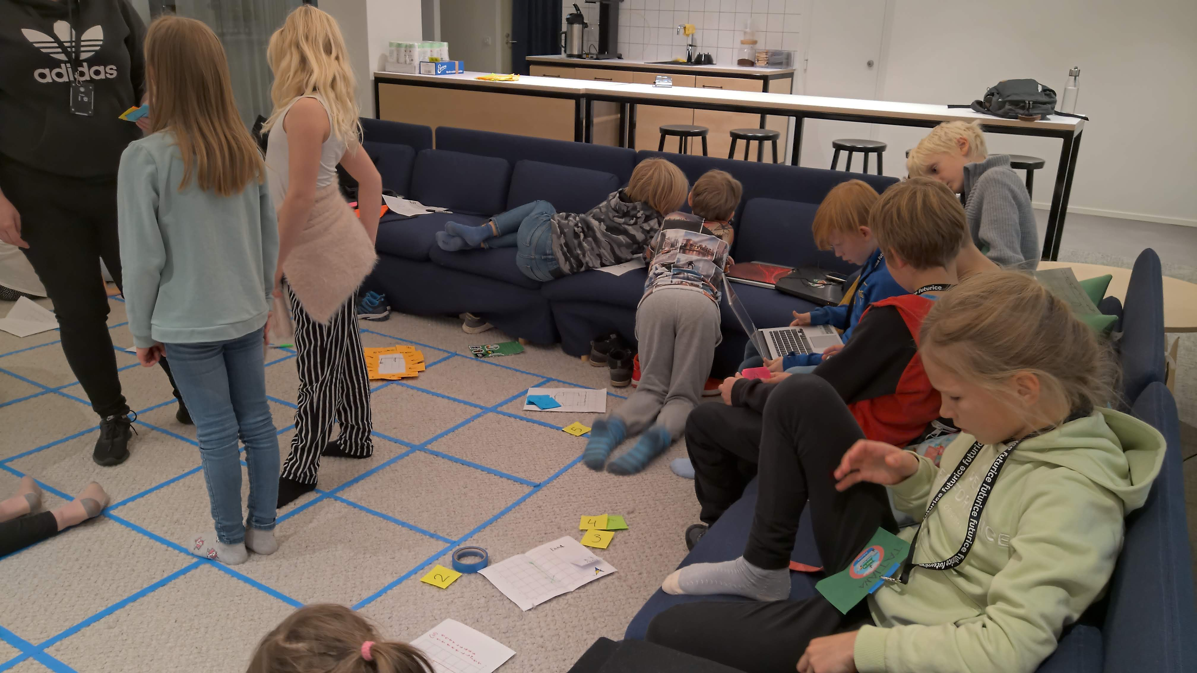 A square grid on the floor made with blue tape, children playing around the floor and sofas