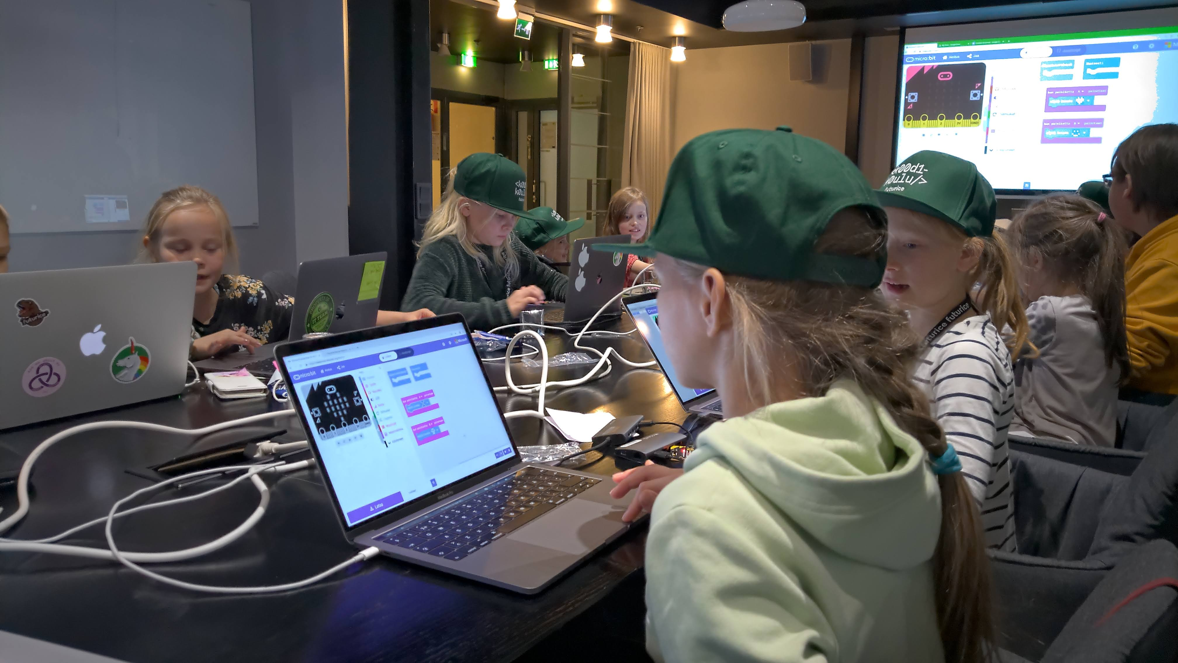 A group of children with green caps sitting in a meeting room working with laptops