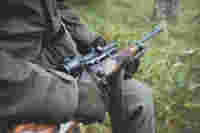 Carrying the rifle scope during hunt. Man sitting waiting in forrest.