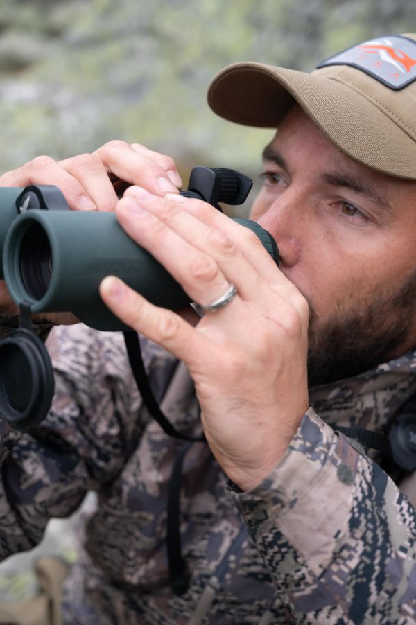 Hunting chamois with the SWAROVSKI OPTIK EL Range TA in the Swiss Alps, hunter looking through the binoculars